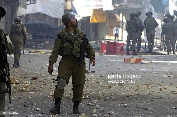 An Israeli soldier looks up as Palestinians throw stones during clashes with in the southern West Bank city of Hebron on September 23 2013 as...