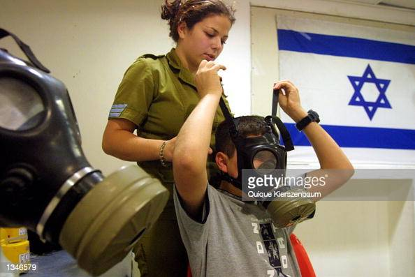 An Israeli soldier measures Leonid Rizaiev for a gas mask at a distribution center in a shopping mall August 21 2002 in Jerusalem Israel Citizens and...