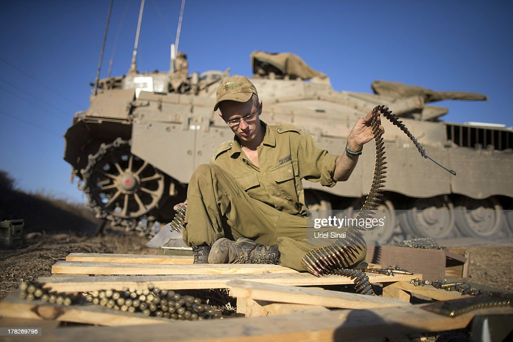 An Israeli soldier organizes his weapons at a deployment area during a military exercise on August 28, 2013 near the border with Syria, in the Israeli-annexed Golan Heights. Tension is rising in Israel amid talks of an international military intervention In Syria following reported chemical weapons attacks.