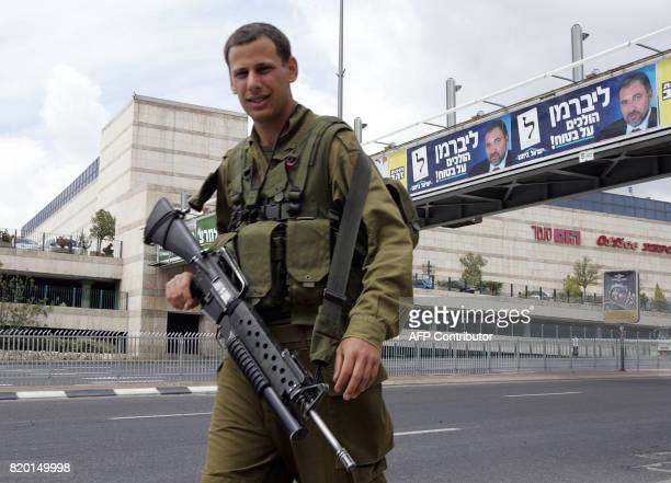 An Israeli soldier patrols 26 March 2006 close to elections posters at a Jerusalem shopping mall The Israeli security forces are on high alert...