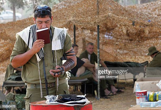 An Israeli soldier performs his morning prayers as others wake up under camouflage netting near the border with the Gaza Strip August 15 2005 in the...