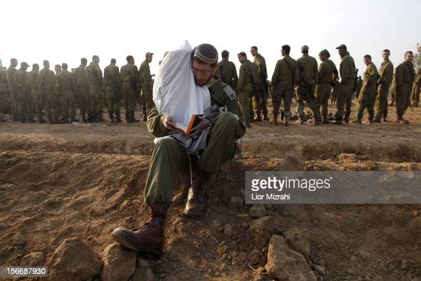 An Israeli soldier performs his morning prayers in a deployment area on November 19 2012 on Israel's border with the Gaza Strip The death toll has...