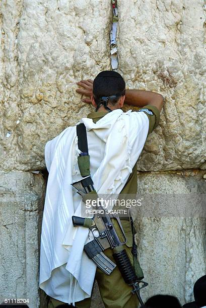 An Israeli soldier prays at the Western Wall in Jerusalem's old city early 27 July 2004 to mark Tisha Be'av the most solemn day in the Jewish...