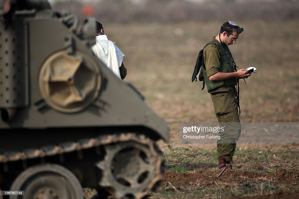 An Israeli soldier prays next to armoured personnel carriers as they wait in a staging area on November 21, 2012 on Israel's border with the Gaza Strip. Despite widespread rumours of a ceasefire militants in the Gaza Strip continue to fire rockets and Israel continues it's bombardment. US Secretary of State Hillary Clinton has arrived in Israel to support and encourage a peace deal being brokered by Egypt.