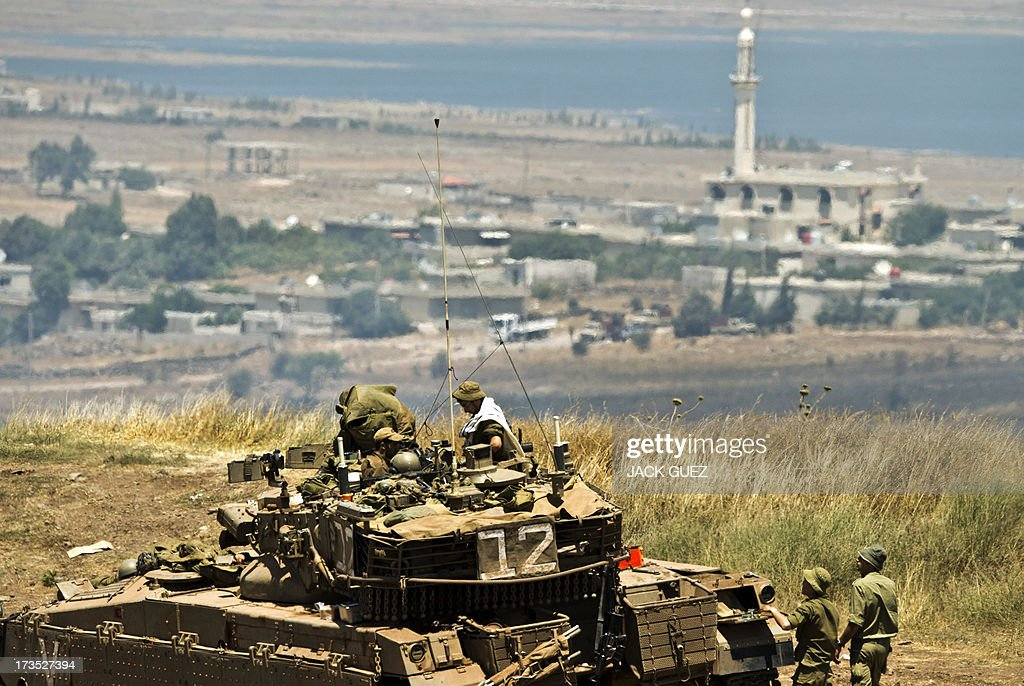 An Israeli soldier prays on top of a Merkava tank stationed in the Israeli annexed Golan Heights near the Quneitra crossing with Syria (background) on July 16, 2013. Mortar fire from inside war-torn Syria hit the Israeli-occupied Golan Heights causing several wildfires to break out along the ceasefire line, an AFP correspondent reported. The apparently stray rounds struck as Syrian rebels and regime forces battled near Quneitra which lies in no-man's land, the correspondent reported.