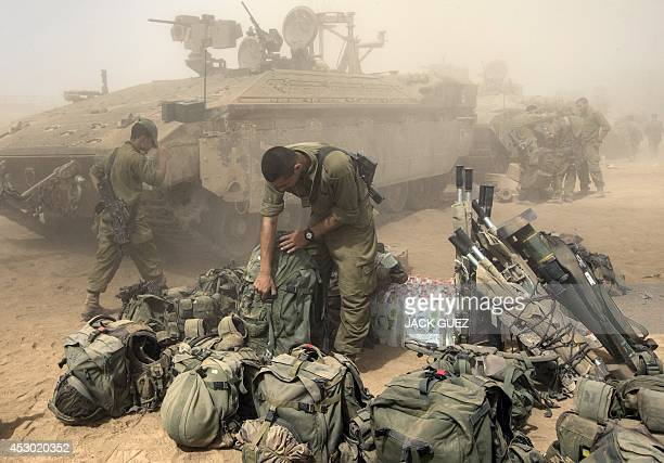 An Israeli soldier prepares his equipment at an army deployment area on the southern Israeli border with the Gaza Strip on August 1 2014 A threeday...