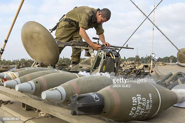 An Israeli soldier prepares his machine gun at an army deployment area on the southern Israeli border with the Gaza Strip on August 1 after the...