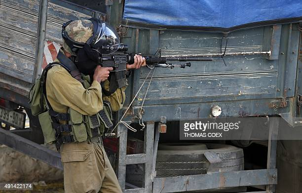 An Israeli soldier prepares to fire towards Palestinian demonstrators during clashes in the West Bank town of Bethlehem on October 5 2015 after...