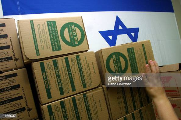 An Israeli soldier reaches for a gas mask kit September 23 2001 at a distribution center in a Jerusalem shopping mall Israelis are lining up at Home...