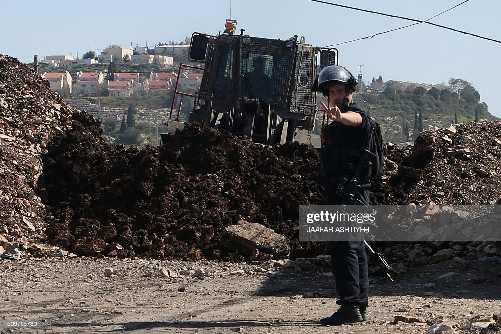 An Israeli soldier reacts as a military bulldozer clears rubble during clashes with Palestinian protesters following a demonstration against the expropriation of Palestinian land by Israel on February 12, 2016 in the village of Kfar Qaddum, near Nablus in the occupied West Bank. / AFP / JAAFAR ASHTIYEH