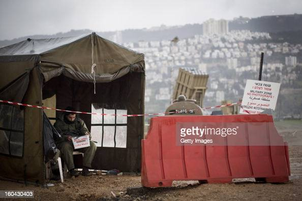 An Israeli soldier reads the newspaper next to an 'Iron Dome' shortrange missile defense system on January 31 2013 near the northern city of Haifa...