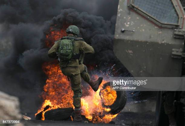 TOPSHOT An Israeli soldier removes burning tires from the road during clashes with Palestinian protesters following a demonstration against the...