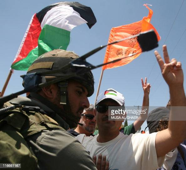 An Israeli soldier restrains a demonstrator during a protest against Israel's controversial separation barrier in the Palestinian village of Maasarah...