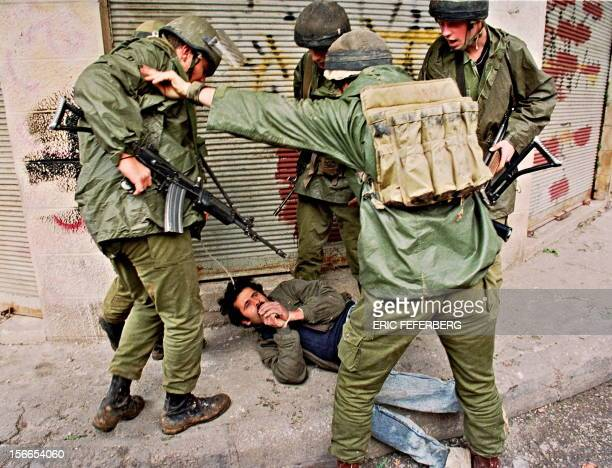 An Israeli soldier restrains another from manhandling an arrested Palestinian who lies on a Nablus street with his hands tied together during violent...