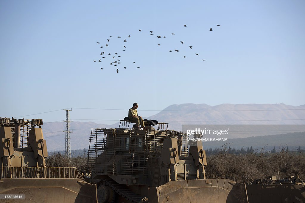 An Israeli soldier rests on his armoured bulldozer in a deployment training area in the Israeli-annexed Golan Heights near the border with Syria on August 28, 2013. Israel will strike back 'fiercely' if Syria attacks the Jewish state, Prime Minister Benjamin Netanyahu said, as the US mulled military action against President Bashar al-Assad's regime.