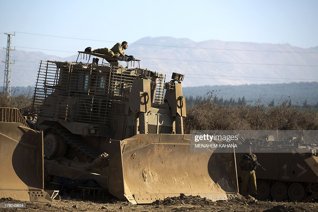 An Israeli soldier rests on his armoured bulldozer in a deployment training area in the Israeli-annexed Golan Heights near the border with Syria on August 28, 2013. Israel will strike back 'fiercely' if Syria attacks the Jewish state, Prime Minister Benjamin Netanyahu said, as the US mulled military action against President Bashar al-Assad's regime. AFP PHOTO/MENAHEM KAHANA