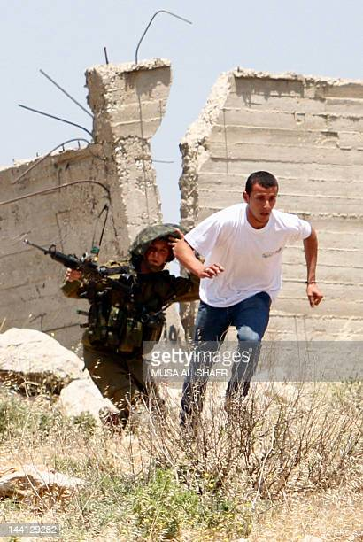An Israeli soldier runs after a Palestinian stonethrower during a protest in AlKhader village near the town of Bethlehem in the occupied West Bank on...