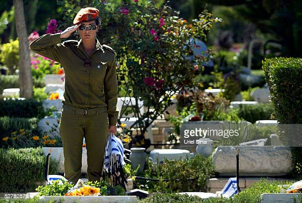 An Israeli soldier salutes after placing a flag over the grave of a soldier at the military cemetery May 10 2005 near Tel Aviv Israel The annual...