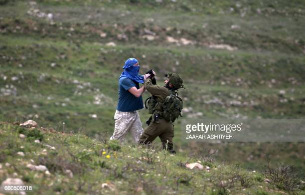 TOPSHOT An Israeli soldier scuffles with a masked Israeli settler while trying to remove him from the area of a protest by Palestinians on March 30...