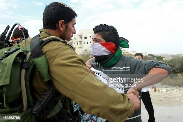 An Israeli soldier scuffles with a Palestinian protester holding a portrait of Ziad Abu Ein a senior Palestinian official who died in a confrontation...