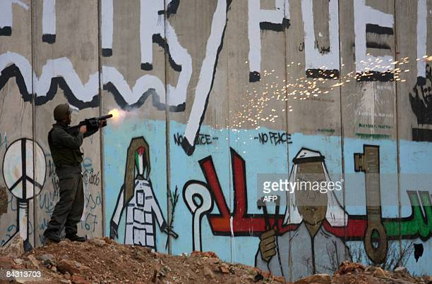 An Israeli soldier shoots tear gas at Palestinian protestors at Qalandia checkpoint between Jerusalem and the West Bank city of Ramallah on January...