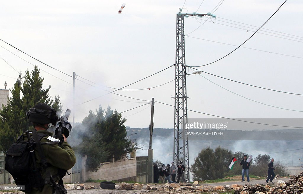 An Israeli soldier shoots tear gas during clashes with Palestinians who protest against the expropriation of Palestinian land by Israel on January 11, 2013 in the village of Kafr Qaddum, near Nablus, in the occupied West Bank.