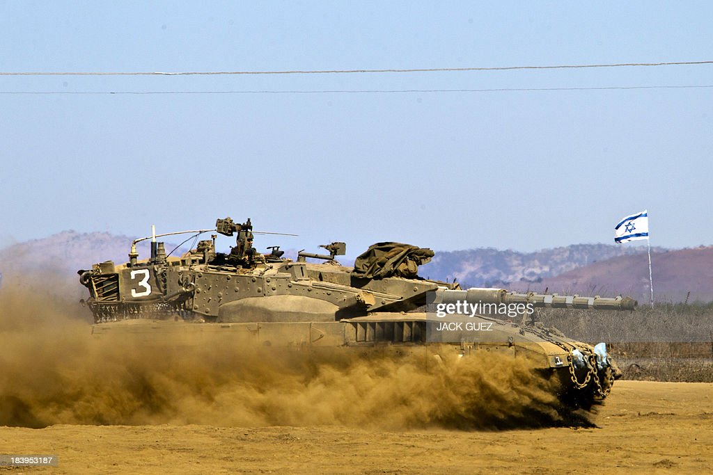 An Israeli soldier sits at the top a Merkava tank as it rolls in a training field in the Golan Heights, next to the Israeli-Syrian border, on October 10, 2013. The Israeli army fired on October 9, a Tammuz missile across the Syrian border in response to mortar fire from the Syrian at an Israeli military base in the northern Israeli-annexed Golan Heights leaving two soldiers with light wounds.