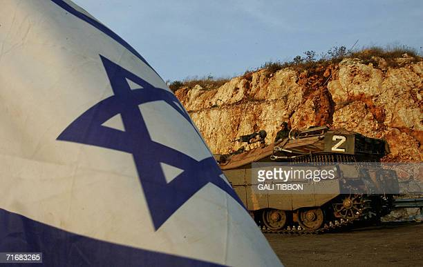 An Israeli soldier sits on a tank 20 August 2006 at a temporary military staging area along the IsraelLebanon border Israel will prevent the Lebanese...