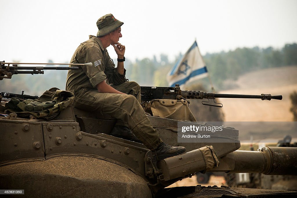 An Israeli soldier sits on a tank on July 28, 2014 near Kafar Azza, Israel. As Israel's operation 'Protective Edge' in Gaza continues, the international community struggles to find a truce agreement.