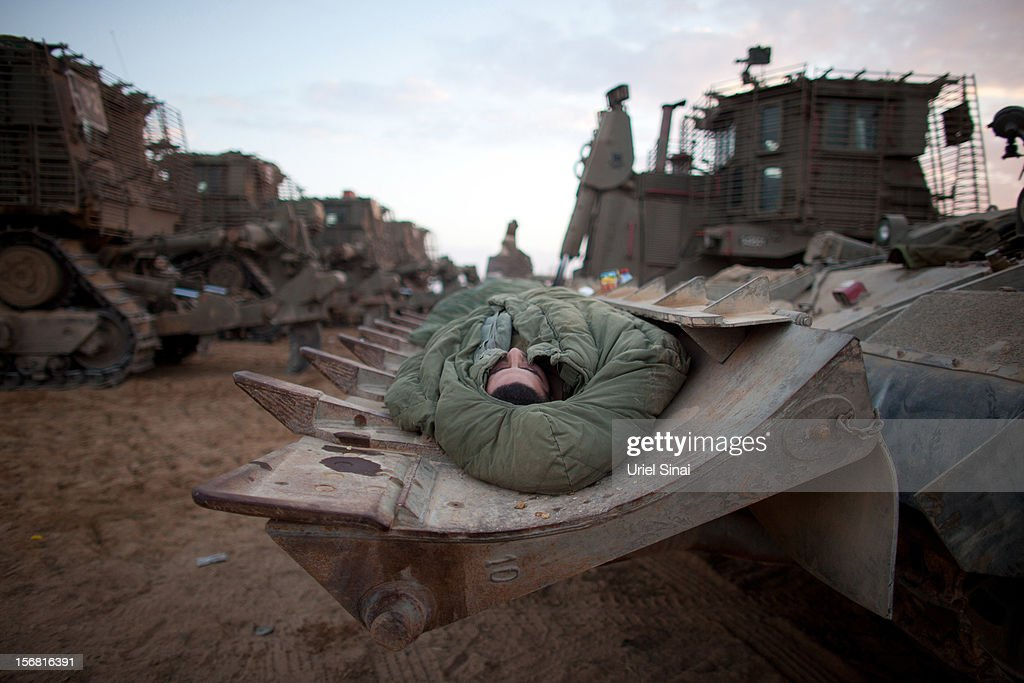 An Israeli soldier sleeps in a deployment area on November 22, 2012 on Israel's border with the Gaza Strip. The ceasefire between Israel and Hamas appears to be holding despite rockets being fired from Gaza. During the night the IDF reportedly arrested a number of 'terror operatives' in the West Bank in continued efforts to restore peace in the region.
