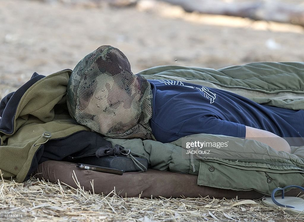 An Israeli soldier sleeps with a mosquito net on his face in a deployment area near Israel's border with the Gaza Strip on July 8, 2014. Israeli warplanes pounded Gaza with more than 50 strikes overnight after Hamas militants fired scores of rockets over the border, dragging the two sides towards a major conflict.