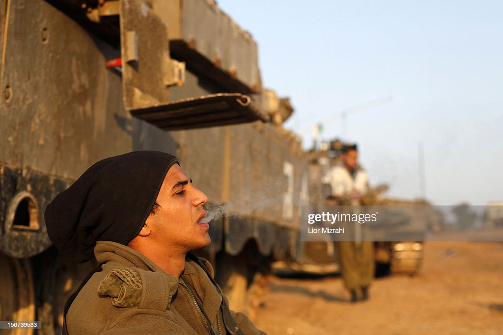 An Israeli soldier smokes a cigarette in a deployment area as the conflict between Palestine and Gaza enters its seventh day on November 20, 2012 on Israel's border with the Gaza Strip. Hamas militants and Israel are continuing talks aimed at a ceasefire as the death toll in Gaza reaches over 100 with three Israelis also having been killed by rockets fired by Palestinian militants.
