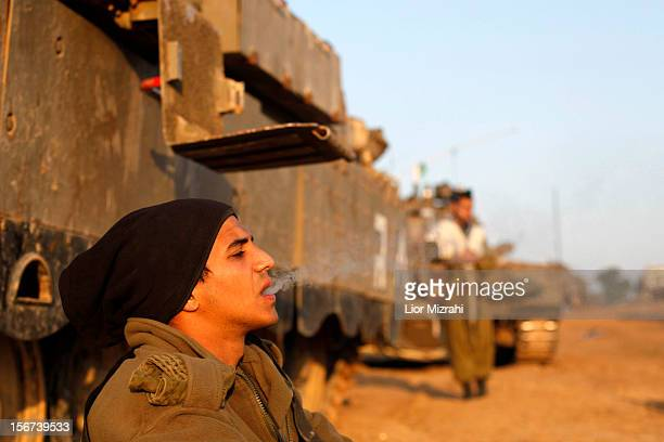 An Israeli soldier smokes a cigarette in a deployment area as the conflict between Palestine and Gaza enters its seventh day on November 20 2012 on...