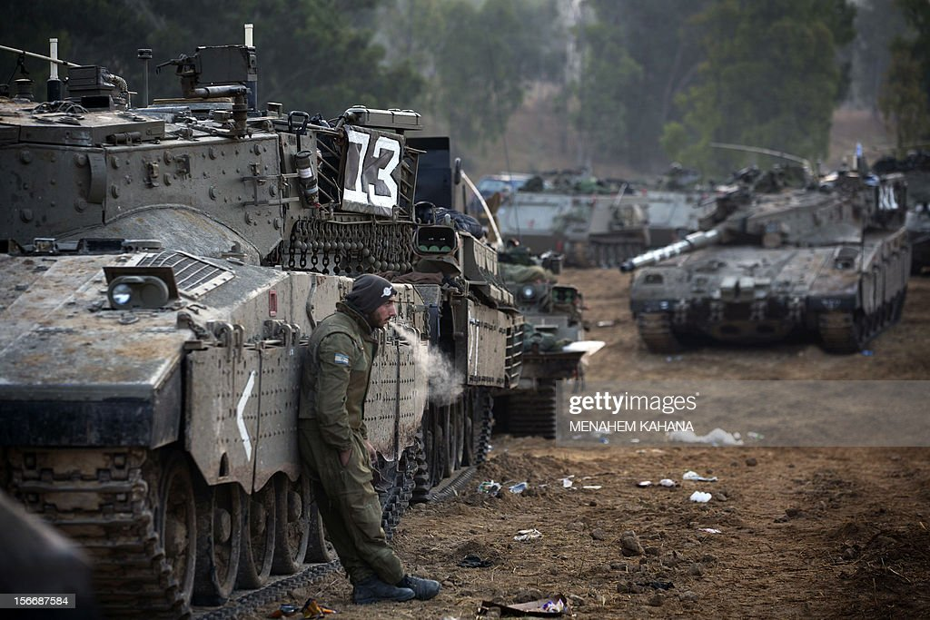 An Israeli soldier smokes a cigarette next to a convey of tanks at an Israeli army deployment area near the Israel-Gaza Strip border as they prepare for a potential ground operation in the Palestinian coastal enclave on November 19, 2012. Israeli air strikes killed 10 Palestinians raising the toll to 87, as Israel pushed raids against Gaza militants into a sixth day amid a flurry of efforts to broker a truce.