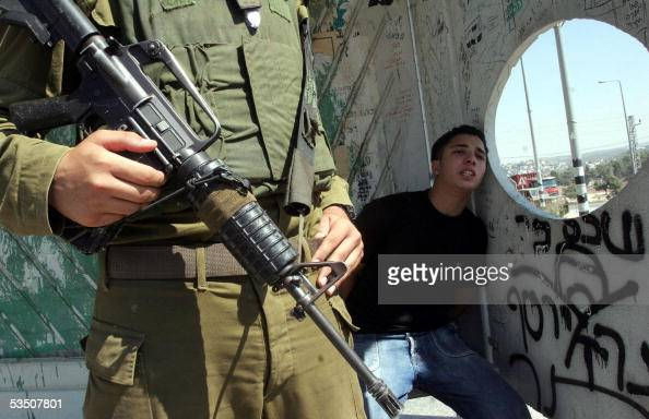 An Israeli soldier stands guard 29 August 2005 next to a detained Palestinian teenager at the Hawara checkpoint close the West Bank city of Nablus...