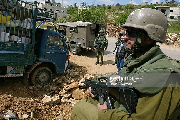 An Israeli soldier stands guard as Palestinians try to retrieve their fullyladen truck which they drove into a ditch April 28 2003 while trying to...