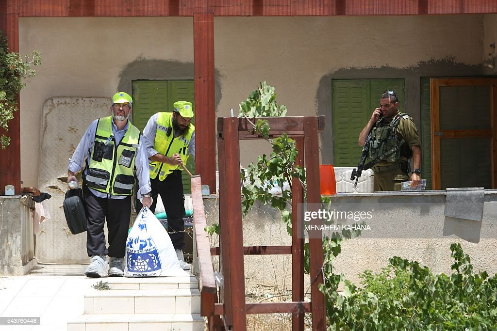 An Israeli soldier stands guard as Zaka volunteers, an emergency response team in Israel, collect human remains in a house in the Jewish settlement of Kiryat Arba in the occupied West Bank where a 13-year-old Israeli girl was fatally stabbed in her bedroom on June 30, 2016. A Palestinian attacker stabbed a 13-year-old girl to death at her home in the Jewish settlement outside the city of Hebron before being shot dead by security guards, the Israeli army said. KAHANA