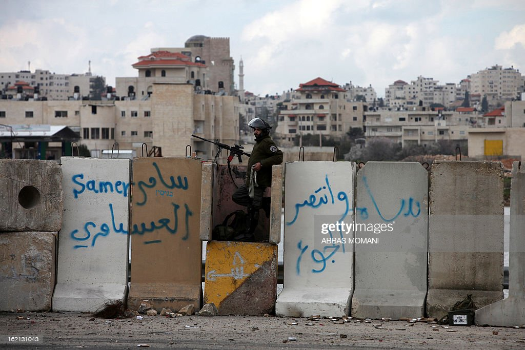 An Israeli soldier stands guard at a concrete barrier near Ramallah on February 19, 2013 as hundreds of Palestinian students protested in support of prisoners on hunger strike in Israeli prisons. Some 800 Palestinians serving time in Israeli jails were refusing food in solidarity with four fellow inmates who have been on long-term hunger strike, officials said. AFP PHOTO/ABBAS MOMANI