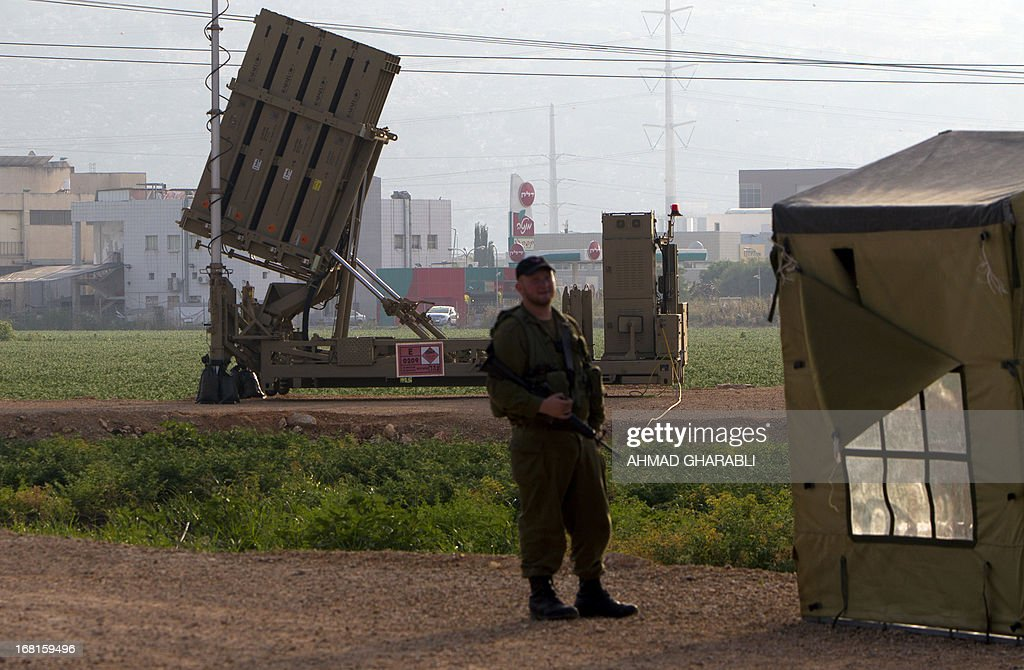 An Israeli soldier stands in front of an 'Iron Dome' short-range missile defence system, designed to intercept and destroy incoming short-range rockets and artillery shells, near the northern Israeli city of Haifa on May 6, 2013. Israeli air raids on Syria at the weekend killed at least 42 soldiers, a watchdog said, fuelling international concern over a spillover of the conflict, as Damascus warned it would strike back.