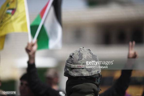 An Israeli soldier stands in front of Palestinian and foreign protesters during a demonstration against Israel's separation barrier in the West Bank...
