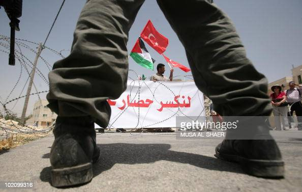 An Israeli soldier stands in front of Palestinian demonstrators holding up their national and the Turkish flags during a protest against Israel's...