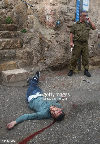 An Israeli soldier stands next to a knife lying on the ground next to the body of a Palestinian man who tried to stab a soldier at the Jewish...