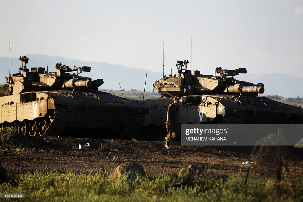 An Israeli soldier stands next to Merkava tanks in the Israeli annexed Golan Heights near the border with Syria on May 5, 2013. Israel carried out a pre-dawn air strike near Damascus, targeting Iranian missiles destined for Lebanon's Hezbollah in the second such raid on Syria in three days, a senior Israeli source said.