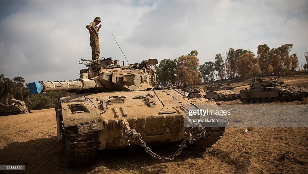An Israeli soldier stands on a tank on July 28, 2014 near Kafar Azza, Israel. As Israel's operation 'Protective Edge' in Gaza continues, the international community struggles to find a truce agreement.