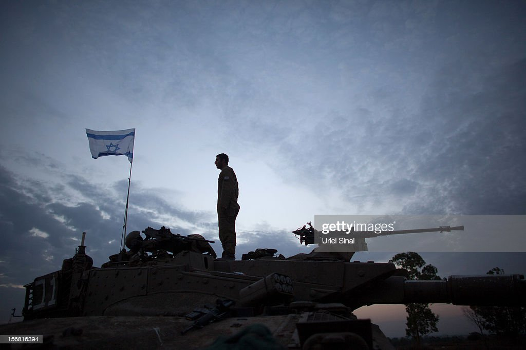 An Israeli soldier stands on his tank in a deployment area on November 22, 2012 on Israel's border with the Gaza Strip.The ceasefire between Israel and Hamas appears to be holding despite rockets being fired from Gaza. During the night the IDF reportedly arrested a number of 'terror operatives' in the West Bank in continued efforts to restore peace in the region.