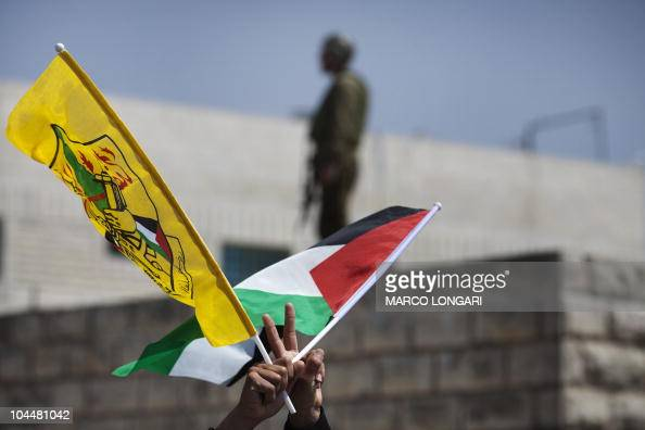 An Israeli soldier stands on the roof of a Palestinian house while a Palestinian protester waves national and Fatah movement flags during a...