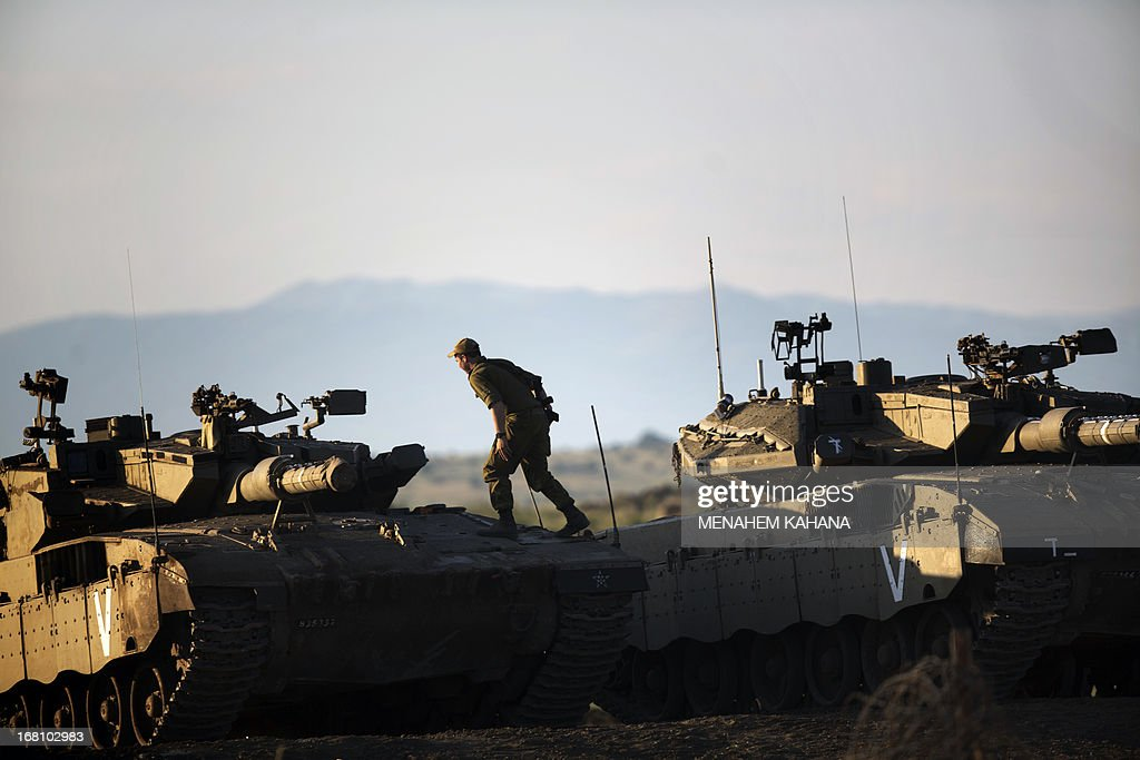 An Israeli soldier stands on top of a Merkava tank in the Israeli annexed Golan Heights near the border with Syria on May 5, 2013. Israel carried out a pre-dawn air strike near Damascus, targeting Iranian missiles destined for Lebanon's Hezbollah in the second such raid on Syria in three days, a senior Israeli source said. AFP PHOTO/MENAHEM KAHANA