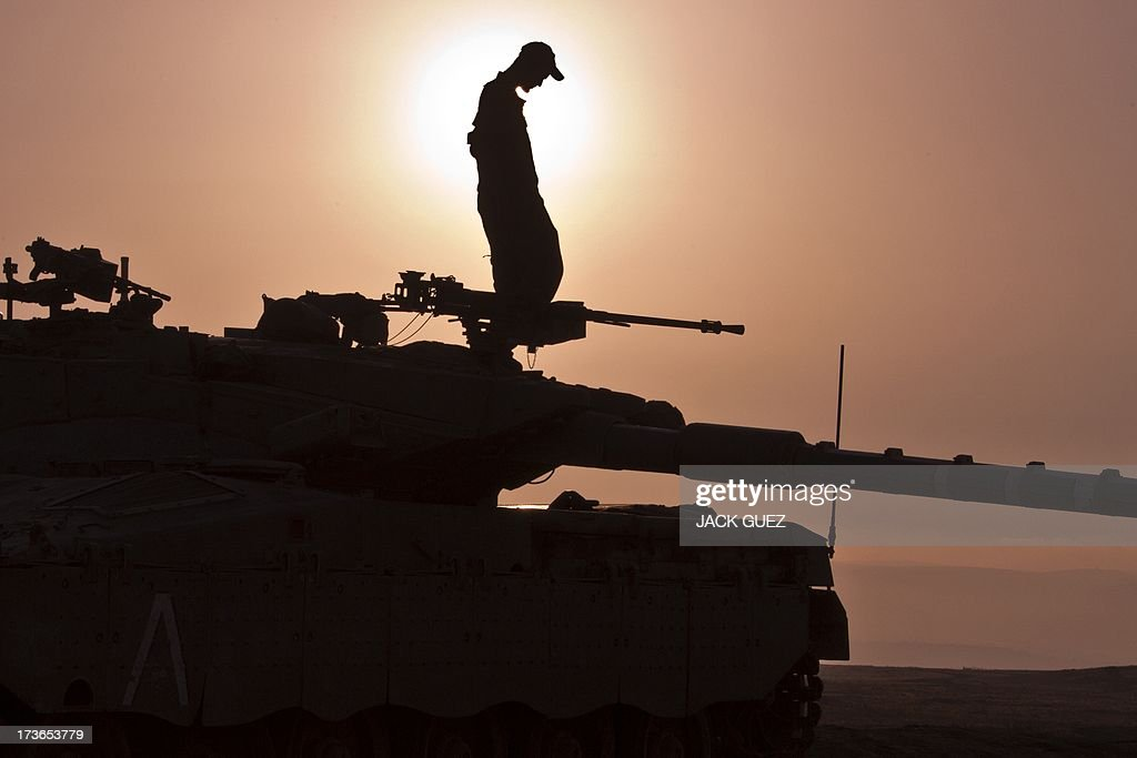 An Israeli soldier stands on top of a Merkava tank stationed in the Israeli-occupied Golan Heights on July 16, 2013 , after mortar fire from inside war-torn Syria exploded in northern Golan, near the border with Syria earlier in the day causing several wildfires to break out. The apparently stray rounds struck as Syrian rebels and regime forces battled near Quneitra which lies in no-man's land, an AFP correspondent reported. Israel, which remains technically at war with Syria, seized 1,200 square kilometres (460 square miles) of the strategic plateau during the 1967 Six-Day War, which it later annexed in a move never recognised by the international community.