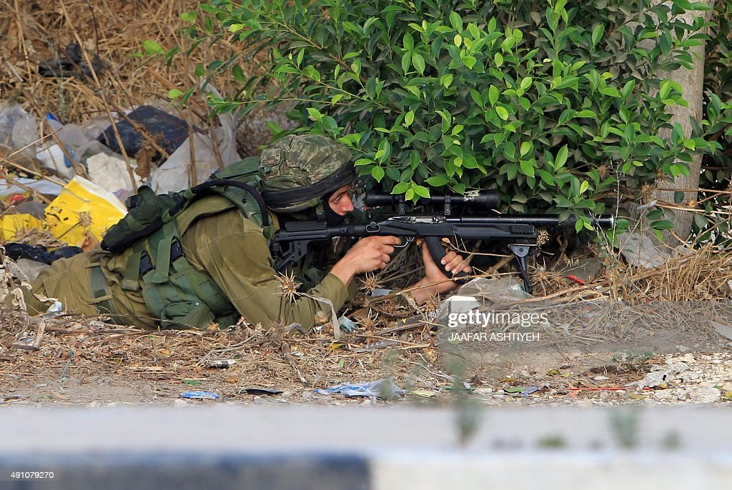An Israeli soldier takes aim during a patrol in a street east of the West Bank city of Nablus on October 3 as the Army searches for the suspected...