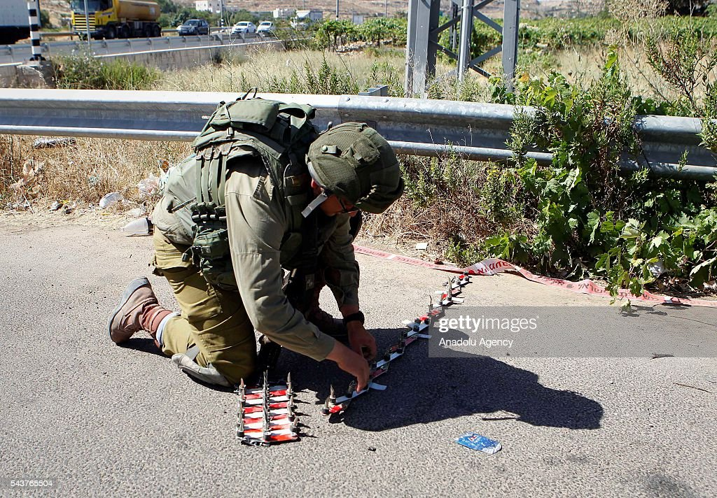 An Israeli soldier takes security measures after a Palestinian, who allegedly attempted a stabbing attack, shot dead by Israeli soldiers in Kiryat Arba town, West Bank on June 30, 2016.